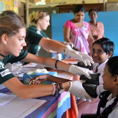 During her high school volunteer trip abroad, a Public Health volunteer measures blood pressure in a medical outreach.